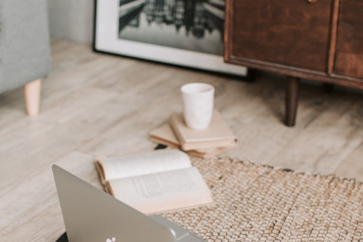 laptop and books on floor carpet